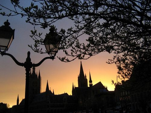 The Cloth Hall and Saint Martin Church are silhouetted against the setting sun in Ypres Belgium