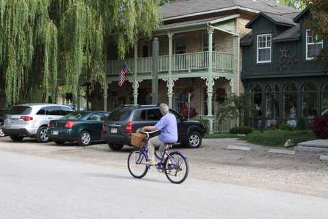A cyclist rides by the lovely Little Inn found on Main Street in Bayfield