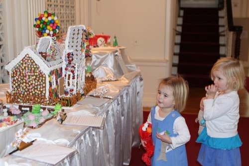 Two and a half year old Jacquie Cook ( and Elmo) and her three year old cousin, Tatum Cook, both of Rochester ,admire this Gingerbread House on display in the museum