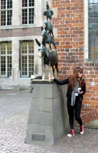 A tourist rubs the Bremen donkey's forelegs for good luck