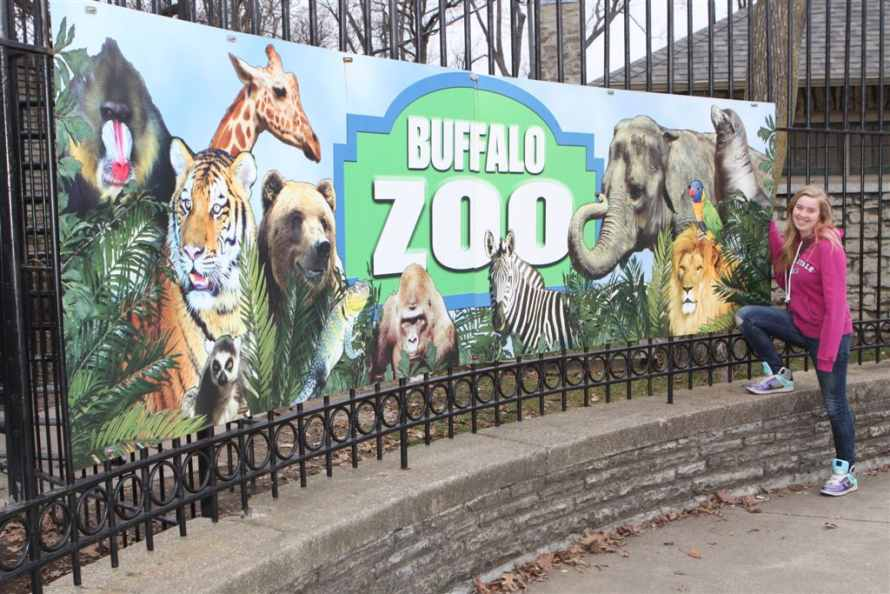 The authors grand daughter, Megan Fisher stands in front of the Buffalo Zoo entrance sign
