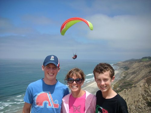 Kathy with sons Andrew and Brendan at the cliffs near Torrey Pines Golf Course near San Diego with a glider passing overhead