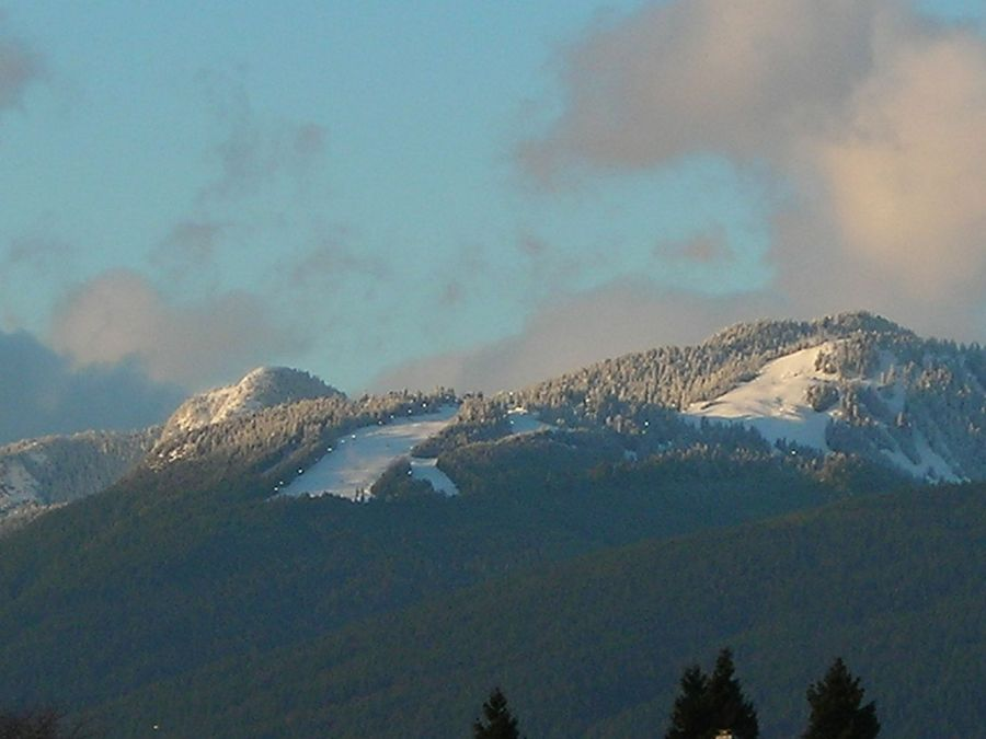 Grouse mountain's snow terrain, as seen from Burnaby, featuring the Cut left and expert peak runs right, Wikimedia Commons
