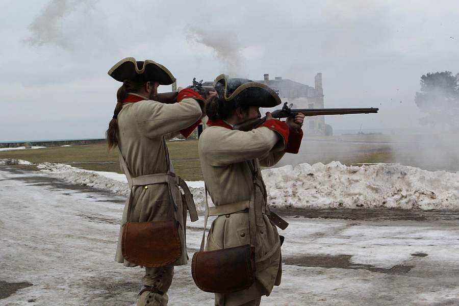 Two French soldier reenactors from the 1750s demonstrate musket firing inside Old Fort Niagara