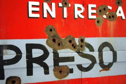 Bullet holes in sign, photo by Mike Keenan